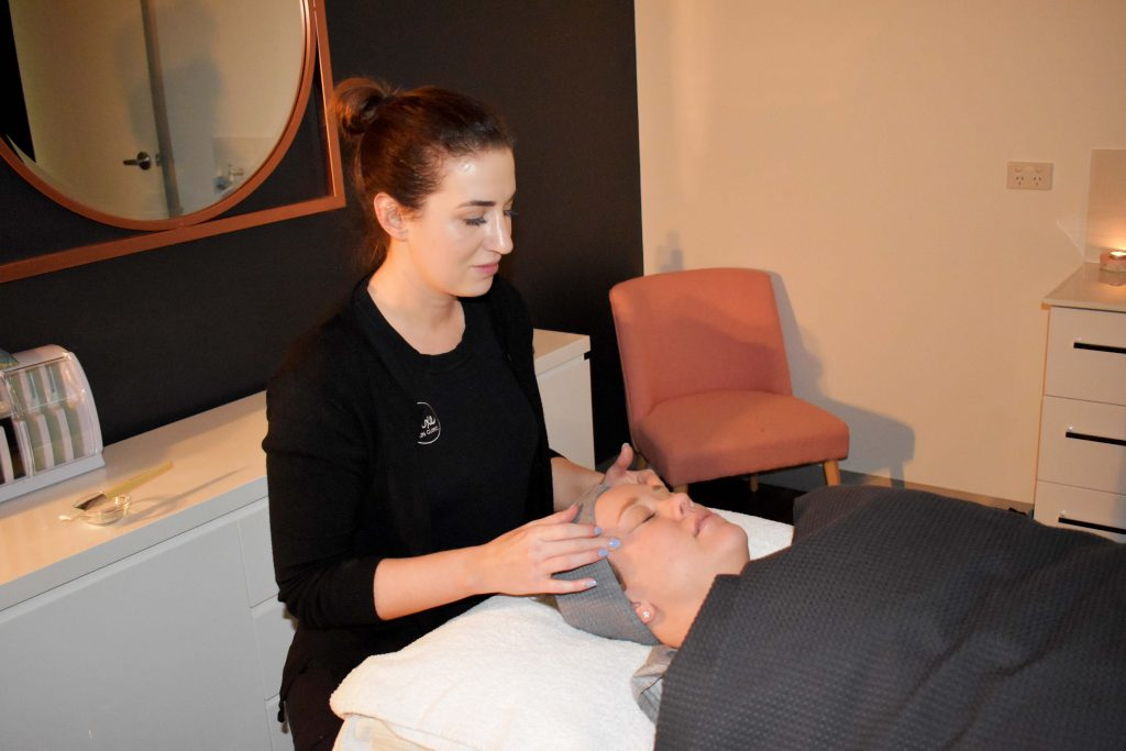 Senior Skin Therapist Joanna Lay gives her client a temple massage at the beginning of her treatment.